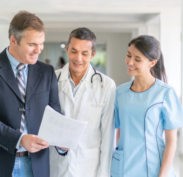 doctors and businessperson talking over a packet of paper