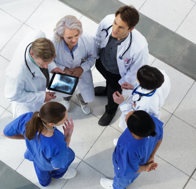 group of doctors talking around tablet